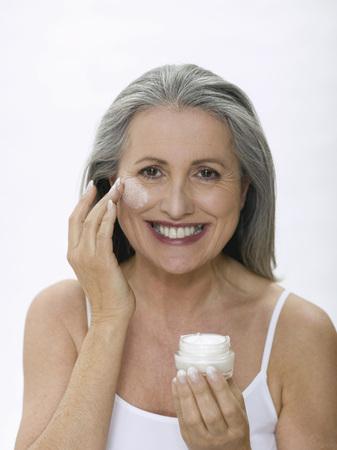cremas faciales: Senior Woman Applying Face Cream, Portrait