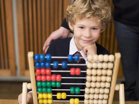 abaco: Boy (4-7) Sitting By Abacus, Hand On Chin, Smiling LANG_EVOIMAGES