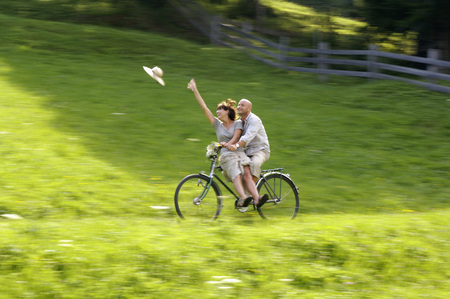 attachment: Couple Riding Bicycle In Meadow, Woman Throwing Hat LANG_EVOIMAGES