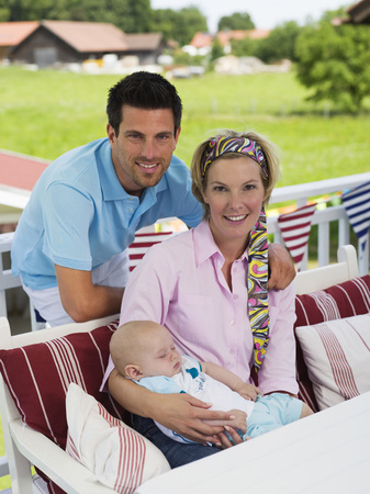 Parents With Baby In Garden LANG_EVOIMAGES