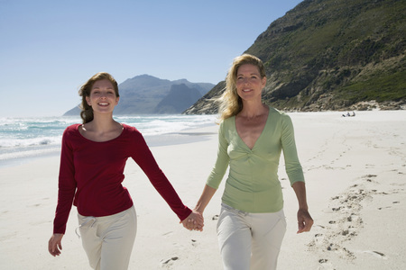 Mother And Daughter Walking On Beach, Hand In Hand