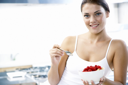 vitamine: Young Woman Holding Bowl With Rasberries LANG_EVOIMAGES