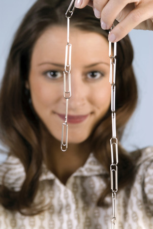 Young Woman Holding Paper Clip Chain, Smiling, Close-Up