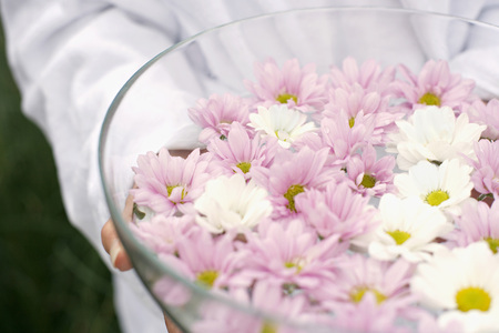 Woman Holding Bowl Of Petals In Water, Close-Up, Mid Section LANG_EVOIMAGES