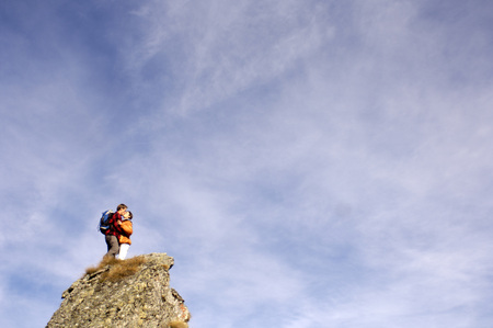 Young Couple Standing On Mountain Peak, Kissing, Side View LANG_EVOIMAGES