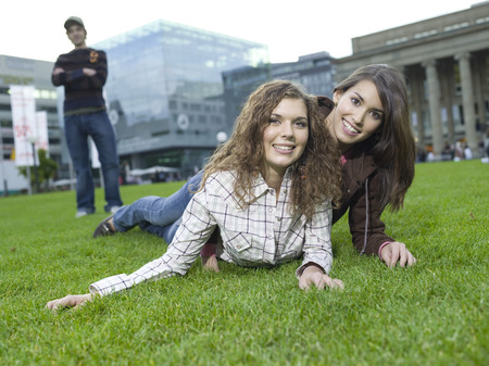 Germany, Berlin, Young Women Lying In Meadow, Young Man Watching In Background