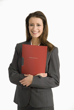 Businesswoman Standing, Holding File, Smiling, Portrait LANG_EVOIMAGES