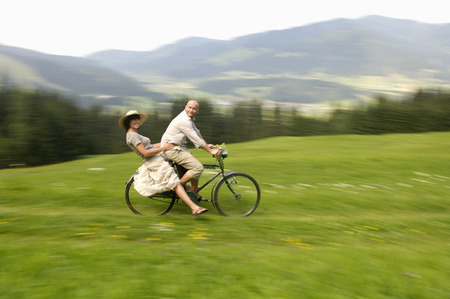 Couple Riding Bicycle In Meadow