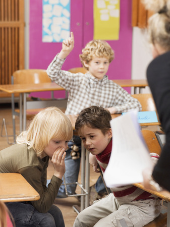 Boy (4-7) Raising Hand In Classroom, Focus On Boys Whispering In Foreground LANG_EVOIMAGES