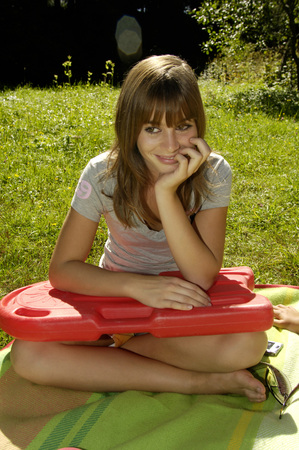 Young Girl Sitting On Blanket, Holding Float