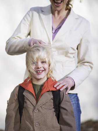 help section: Boy (4-7) Standing In Front Of Mother, Smiling, Close-Up LANG_EVOIMAGES