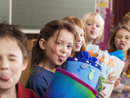 Children (4-7) Holding School Cone, Sticking Out Tongue LANG_EVOIMAGES