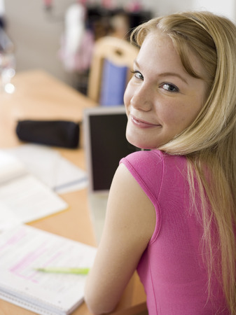 Young Woman Sitting On Desk, Using Laptop LANG_EVOIMAGES