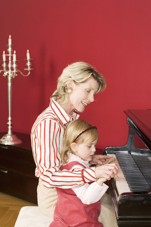 the grand daughter: Grand Mother And Grand Daughter (3-5) Sitting At Piano, Side View