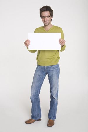Young Man Holding Blank White Board, Portrait LANG_EVOIMAGES