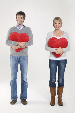 Young Couple Holding Heart-Shaped Cushion, Portrait LANG_EVOIMAGES