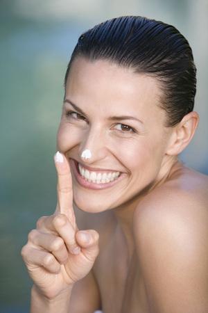 cremas faciales: Mujer joven que aplica la crema facial, retrato LANG_EVOIMAGES