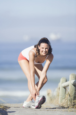 Young Woman Stretching Leg, Smiling, Portrait LANG_EVOIMAGES