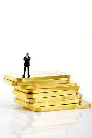 Businessman Figurine Standing On Stack Of Gold Bars