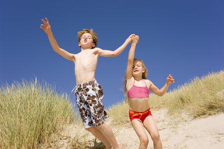 Germany, Baltic Sea, Boy (8-9) And Girl (6-7) Jumping Down Beach Dune