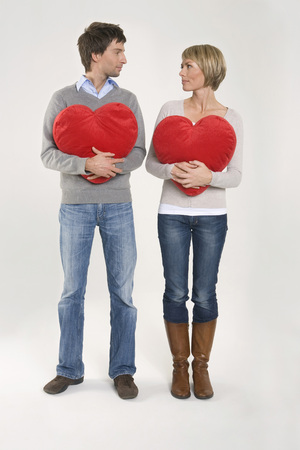 Young Couple Holding Heart-Shaped Cushions, Portrait LANG_EVOIMAGES