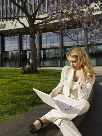 Germany, Baden-Wã¼Rttemberg, Stuttgart, Businesswoman Using Laptop, Man In Background LANG_EVOIMAGES