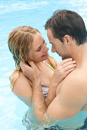 Germany, Young Couple Embracing In Swimming Pool LANG_EVOIMAGES