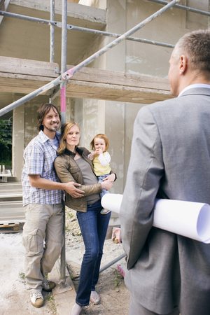 Architect And Young Family At Construction Site