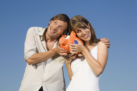 Germany, Bavaria, Young Couple Holding Piggy Bank, Smiling, Portrait