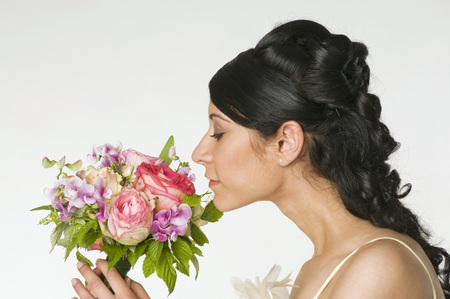 Young Bride Smelling Flowers, Side View, Close-Up LANG_EVOIMAGES