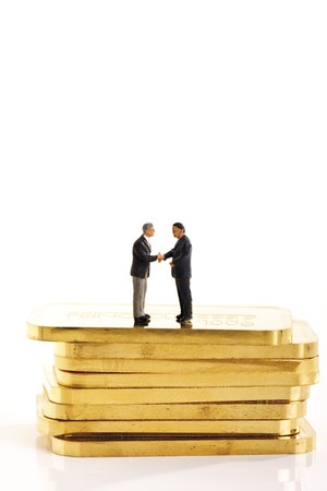 Businessmen Figurines Standing On Stack Of Gold Bars LANG_EVOIMAGES
