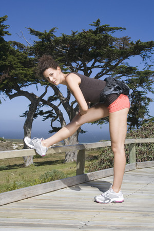 South Africa, Cape Town, Young Woman Stretching Leg, Portrait LANG_EVOIMAGES