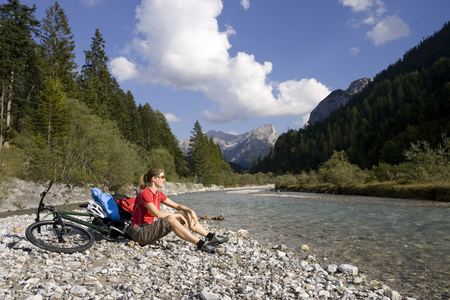 Austria, Tyrol, Ahornboden, Mountainbiker Riding Across Highway