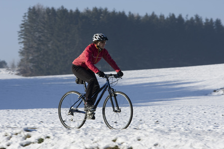 Germany, Bavaria, Oberland, Mountainbiker Riding Across Snow