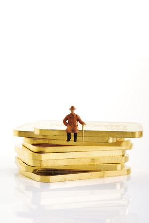 Plastic Figurine Sitting On Gold Bars