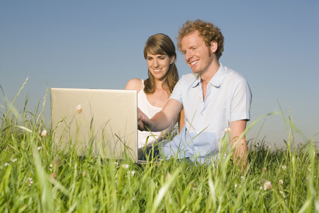 Germany, Bavaria, Young Couple In Meadow, Using Laptop, Portrait LANG_EVOIMAGES