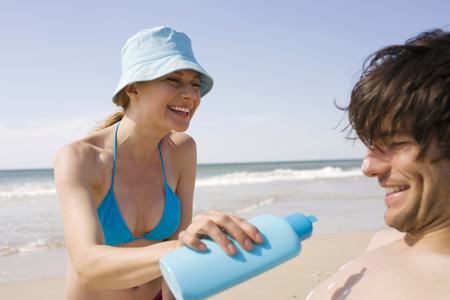 nackte brust: Germany, Baltic Sea, Young Woman Applying Sunscreen To ManS Body, Close-Up LANG_EVOIMAGES