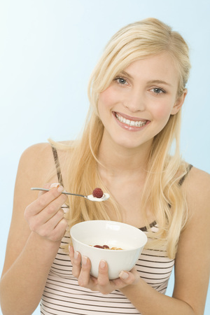 Young Woman Holding Bowl Of Cereal, Smiling