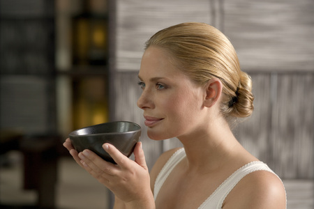 Germany, Young Woman Holding Tea Bowl, Close-Up LANG_EVOIMAGES