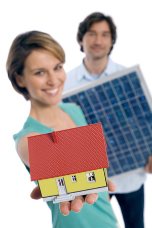 Couple Holding Solar Panel And House
