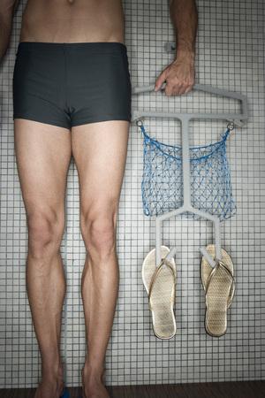 sandalias: Hombre de pie en el vestuario, sosteniendo la suspensión con chancletas, sección baja