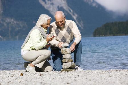 cowering: Germany,Bavaria,Walchensee,Senior Couple Piling Up Stones