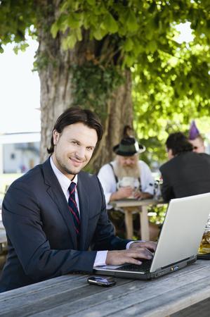 Germany,Bavaria,Upper Bavaria,Young Business Man In Beer Garden Using Laptop,Smiling,Portrait LANG_EVOIMAGES