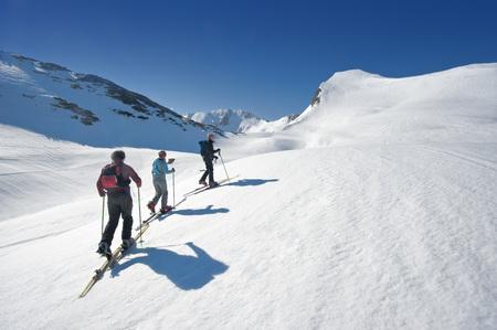 Austria, Salzburger Land, Altenmarkt, Zauchensee, Three Persons Cross Country Skiing In Mountains, Rear View