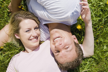 Germany, Bavaria, Munich, Young Couple Lying In Meadow, Smiling, Elevated View, Portrait LANG_EVOIMAGES