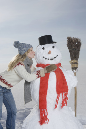 snowcovered: Germany, Bavaria, Munich, Young Woman Kissing Snowman, Portrait
