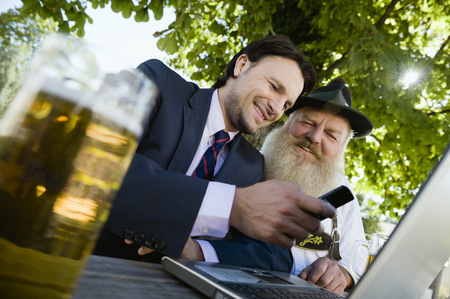 Germany,Bavaria,Upper Bavaria,Senior Bavarian Man And Young Businessman With Laptop In Beer Garden LANG_EVOIMAGES