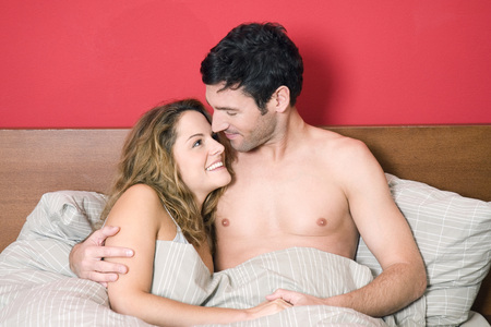 Young Couple In Bed, Smiling, Portrait