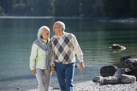Germany,Bavaria,Walchensee,Senior Couple Walking Across Lakeshore LANG_EVOIMAGES