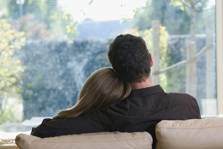 Young Couple On Sofa, Rear View